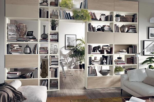 """Le librerie bifacciali delimitano o ridisegnano gli ambienti della casa. <em>Fluida</em> di <a href=""""http://www.scavolini.com"""">Scavolini</a> èadatta soprattutto negli open space: qui in foto fa comunicare soggiorno e cucina lasciano filtrare la <a href=""""http://design.repubblica.it/2016/03/01/con-la-luce-giusta-si-vive-nel-benessere/"""">luce naturale </a>"""