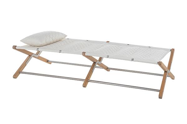 """La brandina <em>Camp Cot</em> di <a href=""""http://www.unopiu.it"""">Unopiù</a> si ispira ai lettini pieghevoli utilizzati dall'esercito italiano nella Prima guerra mondiale. L'idea è del designer Jamie Durie che ha pensato a una solida struttura in legno di teak rivestita di un tessuto trapuntato traspirante, antimacchia e resistente ai raggi UV"""