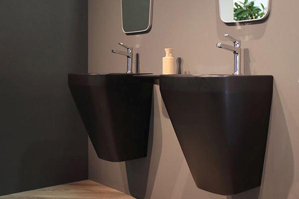 """<em>Baden Baden</em> di <a href=""""https://www.simas.it/"""">Simas</a> è un lavabo sospeso dalla forma trapezioidale qui proposto nella finitura nera opaca"""