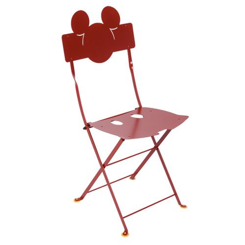 La famosa sedia pieghevole<em>Bistro</em>diFermob in versioneMickey Mouse con le orecchie sullo schienale mentre la seduta presenta due fori che ricordano ibottoni della sua salopette