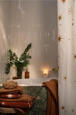 L'atmosfera natalizia si può ricreare anche nella stanza più intima della casa: il bagno. Per H&M Home bastano pochi dettagli: i rami di eucalipto, la luce calda delle candele, asciugamani e tende per la doccia che citano le tradizionali stelle, un classico tema delle festività