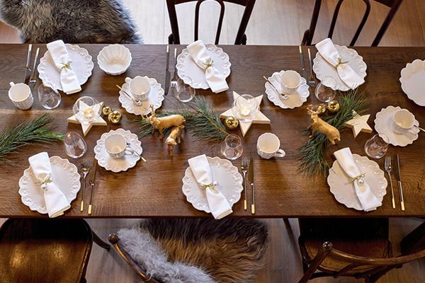 """<em>La tavola rustica</em> - Dedicata a chi ama il fascino della campagna e della natura. <a href=""""https://www.villeroy-boch.it/"""">Villeroy&Boch</a> esalta lo stile country chic con decorazioni naturali, come i rami sempreverdi di stagione, e il legno naturale del tavolo a vista poiché privo di tovaglia o runner"""
