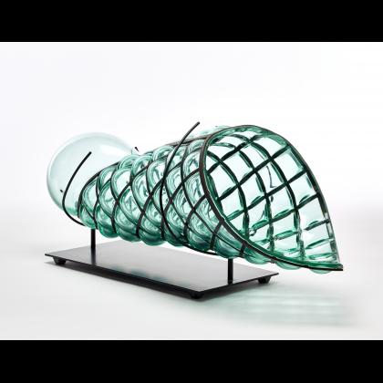 """<em>GAE AULENTI</em> - """"Ritorto"""", Vaso scultura. Venini, Murano, 1995. Vetro verdino trasparente soffiato in griglia metallica. Firmato a punta """"Venini 1980"""" e recante etichetta adesiva della manifattura. Completo di supporto metallico (cm 64x20x22,5 - lievi difetti). In asta: 20 dicembre 2018 ore 15. Valutazione 1.200 - 1.500 euro"""