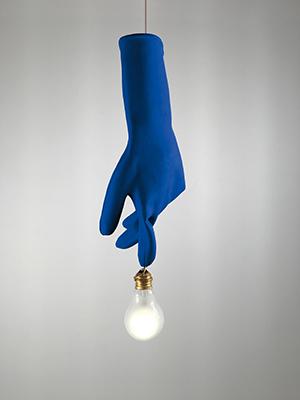 """Un'ideafuori dal comune. Èla lampada a sospensione <em>Blue Luzy</em>di<a href=""""http://www.ingo-maurer.com"""">IngoMaurer</a>: un guanto in gomma con lampadina smerigliata sulla punta del dito indice. È disponibile nella colorazione blu o nera (480 euro)"""