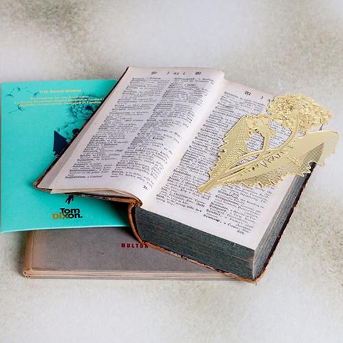 """Per gli amanti della lettura il segnalibro firmato da <a href=""""https://www.tomdixon.net/"""">Tom Dixon</a>. <em>Dandelion</em> è realizzato in un sottile foglio di ottone traforato al laser, le sue lavorazioni si ispirano ai fiori essicati, quelli dimenticati tra le pagine di un libro (10 euro)"""