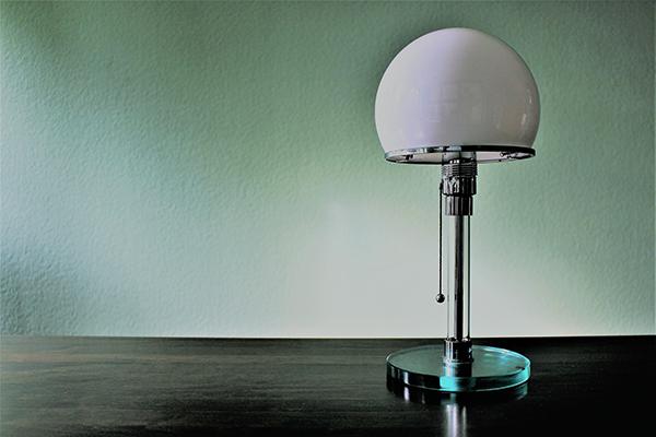 Al prototipo di questa lampada lavorarono Wilhelm Wagenfeld e Carl Jucker, che se ne contesero la paternità