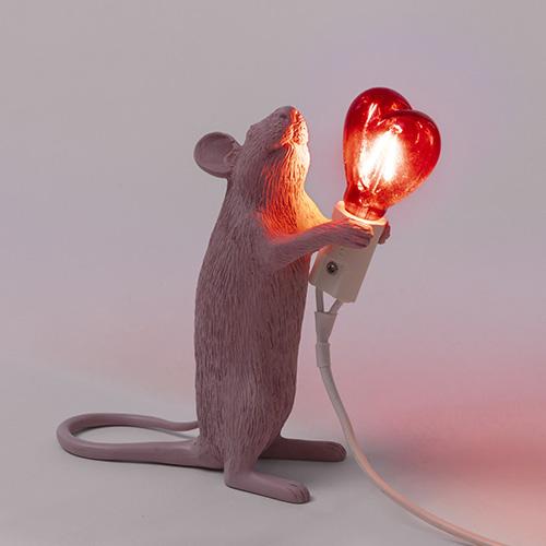 """In occasione del San Valentino <a href=""""https://www.seletti.it/"""">Seletti</a> ha lanciato una edizione limitata della <em>Mouse Lamp</em>: il simpatico topolino in resina si tinge di un colore cipria e tiene tra le zampe una lampadina rossa a forma di cuore (89 euro)"""