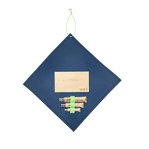 """Il <em>Nomad cooking kit</em> di <a href=""""https://www.opinel.com/"""">Opinel</a> ha tutto il necessario per cucinare all'aria aperta: un coltello cavatappi, un pelaverdure, un coltello a lama seghettata, un tagliere in legno e un panno in microfibra che serve anche come tovaglietta (59 euro)"""