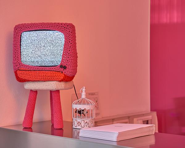 Divertente e colorato il televisore catodico decorato in maglia crochet nei toni del rosa e del rosso
