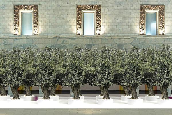 """L'artista olandese Sabine Marcelis firma la seconda edizione di <em>The Green Life</em>, il progetto di <a href=""""https://www.rinascente.it/"""">Rinascente</a> che ha lo scopo di contribuire a rendere le città più belle e più vivibili. Fino al 22 aprile un suggestivo viale alberato di 16 ulivi centenari unisce lo store al Duomo"""
