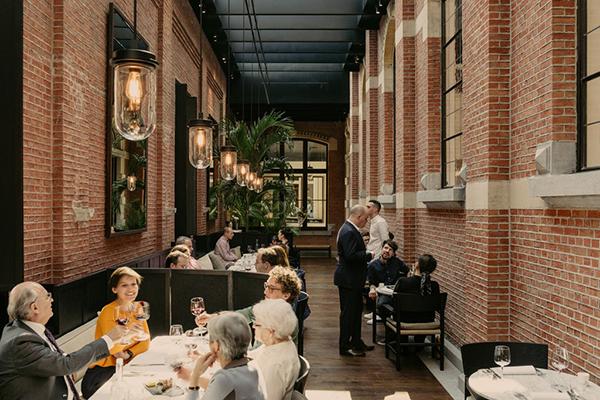 """L'antica chiesa è sede del ristorante stellato """"The Jane"""". Si caratterizza per una grande copertura a vetri che sovrasta le pareti in mattoni affiancate da antichi stucchi (foto Robert Rieger)"""