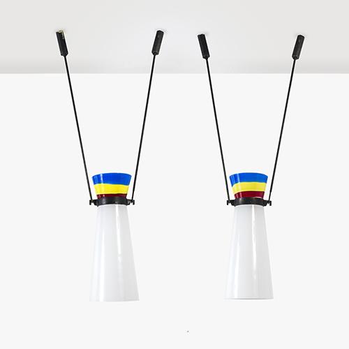 Coppia di lampade a sospensione in vetro incamiciato lattimo con fasce orizzontali colorate. Anni Cinquanta, produzione Venini. Disegno originale realizzato per il negozio Olivetti di New York. Base d'asta 4.000 euro