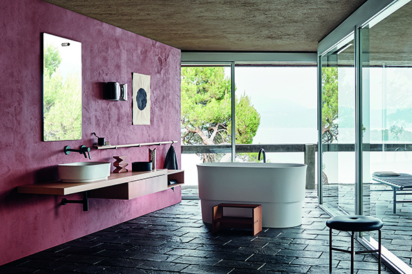 """VASCHE SMALL SIZE -Quando sipensaal relax nella stanza da bagnoil pensiero va subitoa una accogliente vasca. Un desiderio non più così irrealizzabile anche per chi ha un bagno piccolo. Questa edizione del Cersaie dimostra infatti come i formati mini non hanno nulla da invidiare alle sorelle maggiori.<em>Immersion</em> di <a href=""""http://www.agapedesign.it"""">Agape</a> ne è unesempio (nella foto). Lo studio<a href=""""http://thepractice.neriandhu.com/en"""">Neri&amp;Hu</a>hareinterpretato le tradizionali tinozze di legno orientali: occupa una superficie inferiore e ha una profondità maggiore.La vasca permette due differenti posizioni, una più sollevata grazie ad una seduta in legno iroko (o nello stesso materiale della vasca) posizionata su uno dei lati, l'altra completamente immersi favorendo la sensazione di relax, avvolti dal vapore che risale lentamente dalla superficie dell'acqua. La postura più eretta adottata all'interno della vasca ricorda l'esperienza delle stazioni termaliOnsen"""