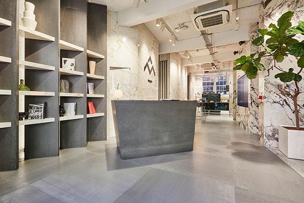 Le grandi lastre in gres vengono presentate come elemento costruttivo delle pareti, delle quinte, delle librerie e della reception