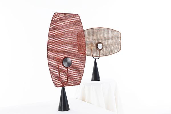 """TERZO PREMIO - lampada Fan <BR><EM>Motivazione della giuria</EM>: è touch con ricarica elettrica a induzione. Ha una stretta relazione con la cultura del bambù e la cultura buddista. Allo stesso tempo, Fan è parola onomatopeica di """"flip"""", il paralume in bambù può essere girato secondo le preferenze personali, ha un certo grado di flessibilità, ma anche due coppie di combinazioni, che danno effetti diversi. Quando si dischiude di notte, una lampadina rotonda a perla illumina la parete, e anche l'intera lampada mostrando i dettagli del paralume in bambù intrecciato e il suo aspetto elegante"""