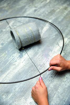 Step 3: avvolgere due lembi di filo di ferro intorno al vaso e fissarne uno su ogni lato nella metà inferiore dell'anello metallico. Importante: tirare i fili ben tesi e attorcigliarne saldamente le estremità (foto Stars For Europe)