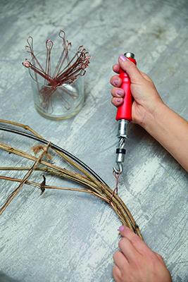 Step 5: appendere l'anello. Disporre le viti di clematis intorno all'anello fissandole con i fili per legature. Se lo si desidera, è possibile colorare le viti con l'oro in precedenza (foto Stars For Europe)