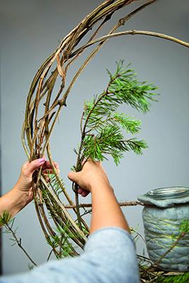 Step 6: arricchire due terzi della struttura realizzata con diversi tipi di fiori, ad esempio ramoscelli di pino, eucalipto, pigne o edera. Fissare i ramoscelli di pino, se necessario, con il twister (foto Stars For Europe)