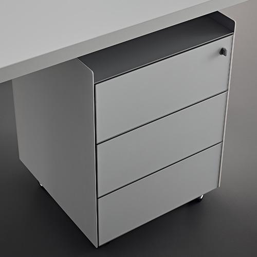"""Tutto sotto controllo: anche una cassettiera può aiutare a tenere in ordine il piano di lavoro e lettura. Se il tavolo ne è sprovvisto si può scegliere una cassettiera, magari su ruote. Qui della linea Flat System di <em><a href=""""https://www.rimadesio.it"""">Rimadesio</a></em>, cassettiera in vetro con tre cassetti"""